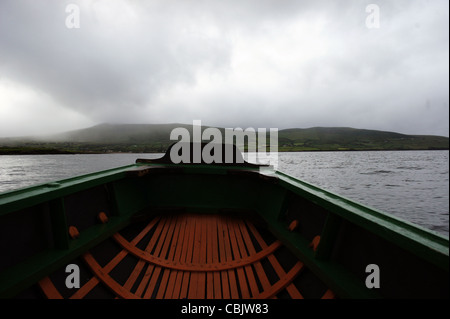 View of Kerry coastline and hills from traditional currach or naomhog rowing boat on the water with dramatic cloudy - Stock Photo