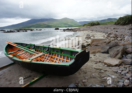 Currach or naomhog, a traditional Irish rowing boat, on a rocky beach in Kerry with green mountains in distance - Stock Photo
