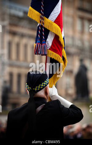 Retired soldier holding a flag at the annual Remembrance Service, George Square, Glasgow, Scotland, UK, Great Britain - Stock Photo