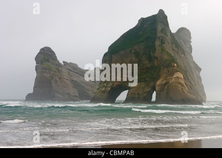 Wharariki Beach and Archway Islands on a misty morning - Stock Photo