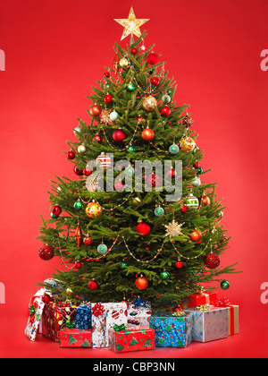 Beautiful decorated Christmas tree with colorful wrapped gifts under it. Isolated on bright red background. - Stock Photo