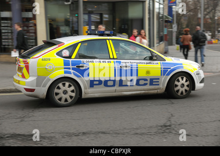 A police patrol car at speed in a busy city. Southampton, Hampshire. December 2011. - Stock Photo