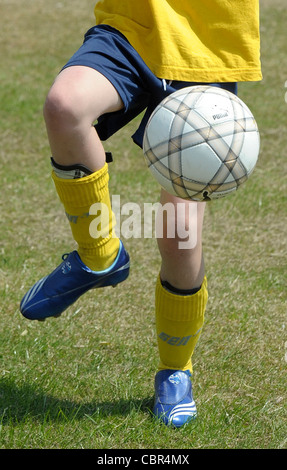 A cropped generic image of a soccer player showing the ball at the players feet. - Stock Photo