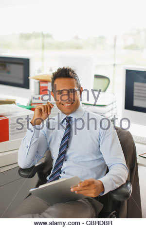 Businessman sitting at desk holding clipboard - Stock Photo