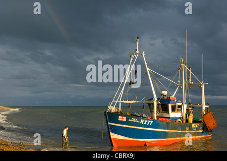 Hastings, East Sussex, England. Red and blue fishing boat Four Brothers coming to shore in the afternoon sun with - Stock Photo