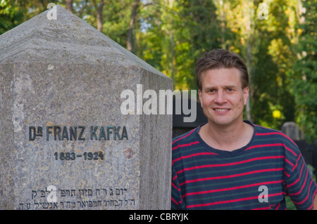 Tourist at grave of Franz Kafka in Novy zidovsky hrbitov the New Jewish cemetery Zizkov district Prague Czech Republic - Stock Photo