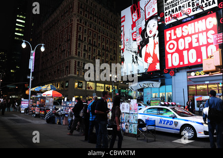 Night neon shot billboards, buildings, people, NYPD car parked sidewalk art stall, West 42nd Street at Broadway, - Stock Photo