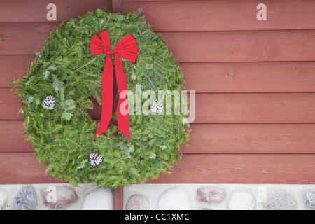 A Christmas evergreen wreath with a red bow on the side of a log and fieldstone cabin wall. - Stock Photo