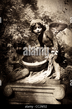 Two statues of young boy angels in Brompton Cemetery, London - Stock Photo