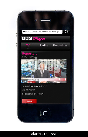 Watching the BBC News Channel on the BBC iPlayer on an Apple iPhone 4 smartphone - Stock Photo