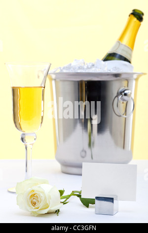 Photo of a white rose on a table with white tablecloth and a glass of champagne plus bottle in an ice bucket in - Stock Photo