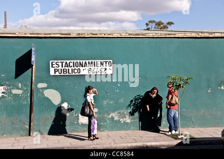 stylish young woman in high heels waiting at bus stop with other people in front of lovely old blue wall on beautiful - Stock Photo
