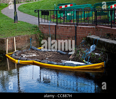 Oil spill spillage pollution in river pollution control environmental Oil booms oil absorbent granules in use - Stock Photo