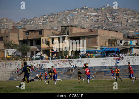 A football team competes on the pitch in Lima, Peru, South America. - Stock Photo