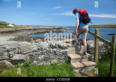Walker crossing a stile on the Ballyhornan Coastal Path, Lecale Way, County Down, Northern Ireland. - Stock Photo