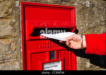 Close up of a hand introducing a letter in a Traditional Royal Mail Letter Box in wall of Edinburgh, Scotland, UK - Stock Photo