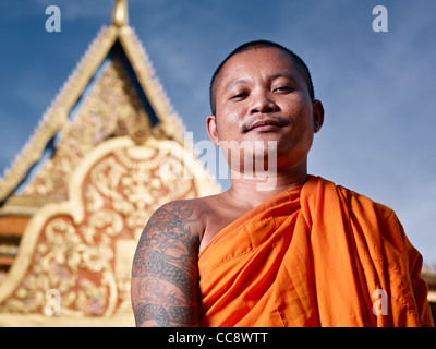 Mid adult Asian monk smiling at camera in buddhist monastery, Phnom Penh, Cambodia, Asia. Low angle - Stock Photo