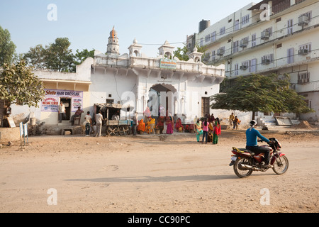 Group waiting near the Ajmer Bus Stand as a mototcyclist drives by in Pushkar - Rajasthan, India - Stock Photo