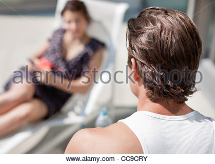 Man watching woman on lounge chair - Stock Photo
