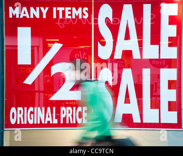 Half price sale posters in a shop store window, UK - Stock Photo