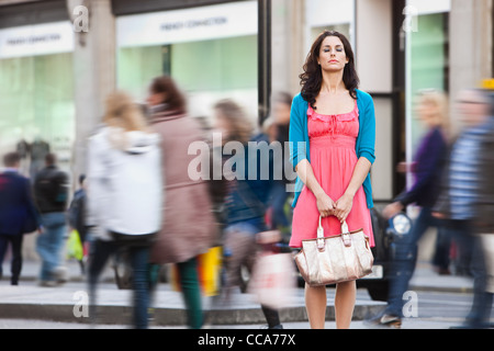 Mid adult woman in pink dress standing still in crowded city - Stock Photo