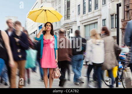 Mid adult woman in pink dress standing still with umbrella in crowded city - Stock Photo