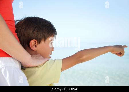 Boy pointing at sea - Stock Photo