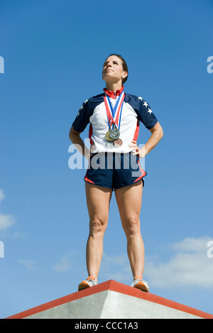 Female athlete standing on winner's podium - Stock Photo