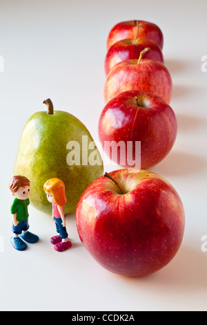 Toy girl and boy discuss nutrition and healthy choices in front of green pear standing out from a line of red apples. - Stock Photo