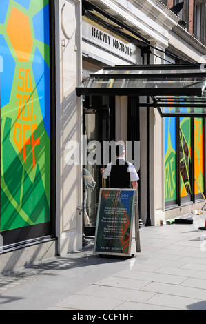 Doorman at entrance to Harvey Nichols retail department store & colourful summer sale shop window posters Knightsbridge - Stock Photo