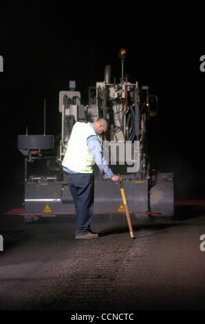 Mechanic John Abdilla (cq) measures the depth of a rumble strip from the white line while putting rumble strips - Stock Photo