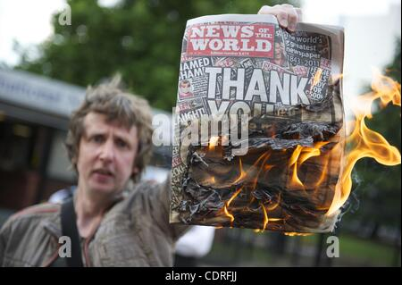 July 10, 2011 - London, England, United Kingdom - A protester burns copies of The News of the World outside News - Stock Photo
