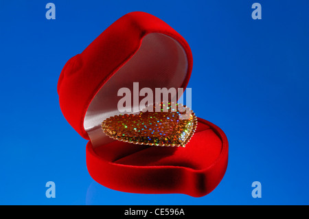 Shiny golden heart in a red jewelry box isolated on blue background - Stock Photo