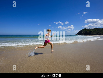 Girl doing a training session on the beach - Stock Photo