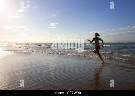 Girl running on the beach - Stock Photo