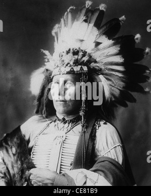 Little Soldier, Sioux Warrior, half-length portrait, facing left, wearing breastplate and war bonnet, circa 1899 - Stock Photo