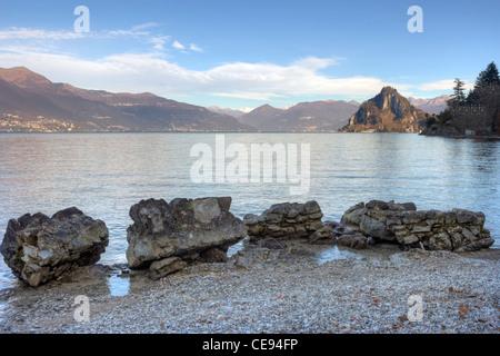Bay named Cinque Arcate on Lake Maggiore in Lombardy, Italy near Laveno. The limestone Rocca di Calde in the background. - Stock Photo
