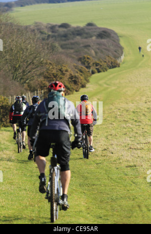 Young people cycling on mountain bikes bicycles off road in a field trail bridleway South Downs National Park - Stock Photo