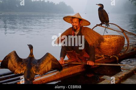 Smiling cormorant fisherman with birds on a bamboo raft on the Li river at dawn Xingpingzhen Yangshuo, Guilin, Guangxi - Stock Photo