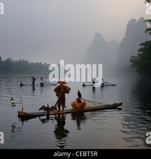 Cormorant fishermen in bamboo rafts at sunrise on the Li river with Karst mountain peaks near Xingping China - Stock Photo