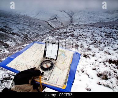 Map and compass work on winter walk, Kinder Scout, Peak District National Park - Stock Photo