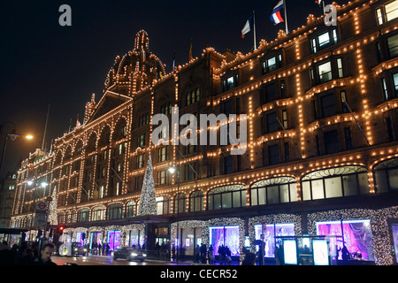 united kingdom london knightsbridge brompton road harrods store illuminated at night - Stock Photo