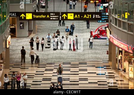 Passengers walk through the transit hall in terminal 3 at Changi Airport in Singapore - Stock Photo