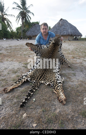 Environmental photographer holding a Jaguar pelt, shot by ranchers after it strayed onto the farm, Guyana, South - Stock Photo