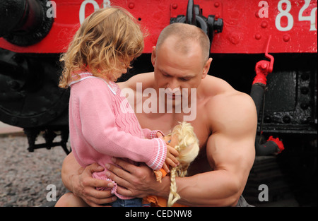 strong shirtless man sits on railroad with little girl - Stock Photo