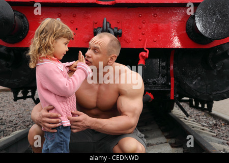 strong shirtless man sits on railroad with little girl, how old are you? - Stock Photo