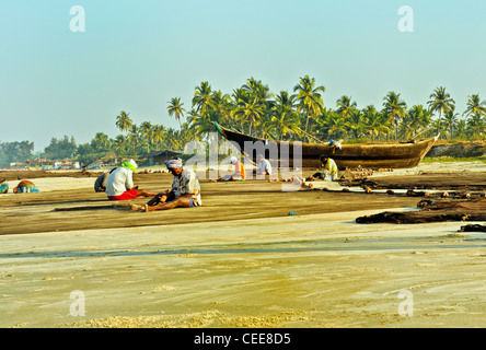 Fishermen repairing fishing nets on Varca Beach, Goa, India - Stock Photo