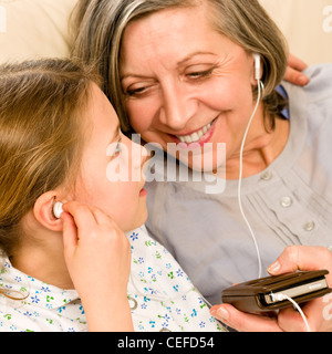 Granddaughter and grandmother listen to MP3 music headphones together smiling - Stock Photo