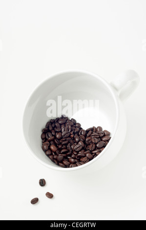 Three beans spill out of heart shaped group of coffee beans nestled in large white coffee cup. - Stock Photo