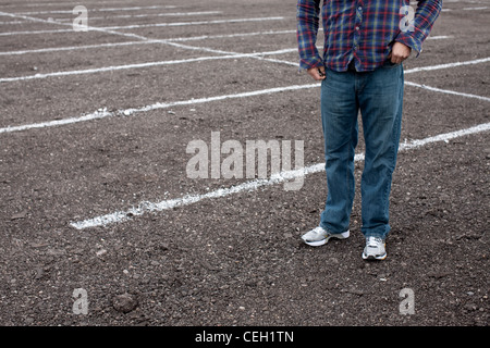 Anonymous man standing in empty parking lot - Stock Photo
